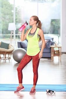 Joven mujer deportiva bebiendo agua en casa