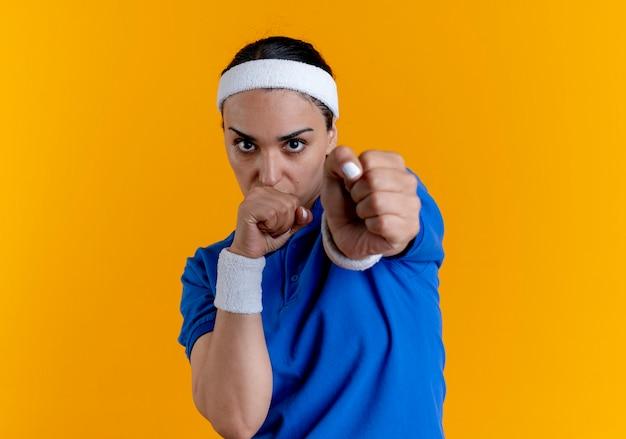 Joven mujer deportiva caucásica confiada con diadema y muñequeras mantiene los puños pretendiendo perforar naranja con espacio de copia