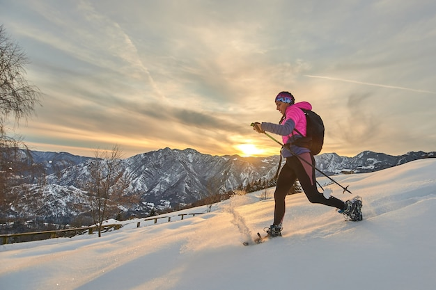 Joven mujer deportiva cuesta abajo en la nieve con raquetas de nieve en un paisaje al atardecer