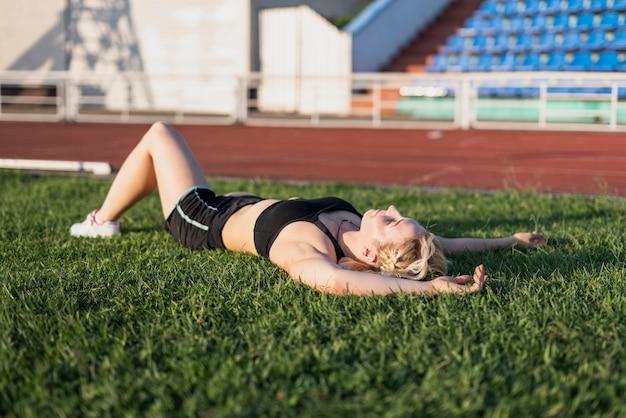 Joven mujer deportiva descanso sentado en el césped