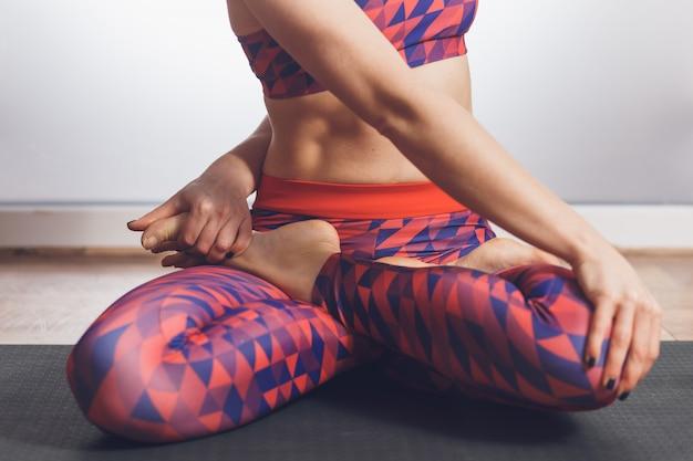 Joven mujer deportiva haciendo ejercicio padmasana