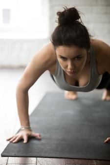 Joven mujer deportiva haciendo ejercicio de prensa ups, estudio loft blanco