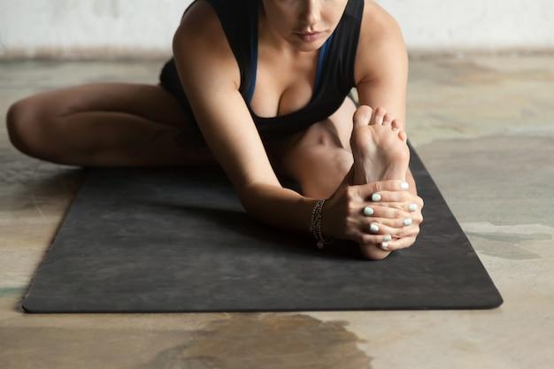 Joven mujer deportiva en janu sirsasana pose, fondo de estudio