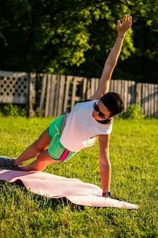 Joven mujer deportiva con pelo negro corto haciendo tabla sobre una estera de yoga al aire libre, entrenando en un parque en la naturaleza