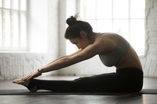 Joven mujer deportiva practicando pilates spine estiramiento hacia adelante ejercicio