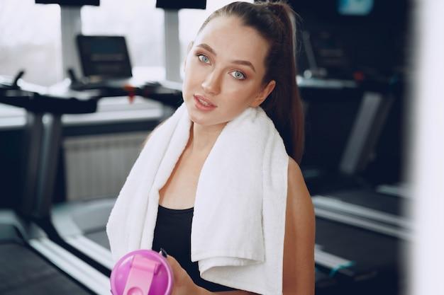 Joven mujer deportiva tomando una copa en un gimnasio después del entrenamiento, cerrar