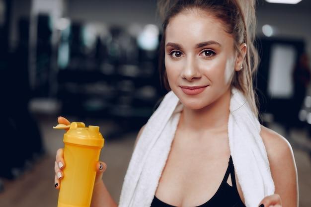 Joven mujer deportiva tomando una copa en un gimnasio después del entrenamiento