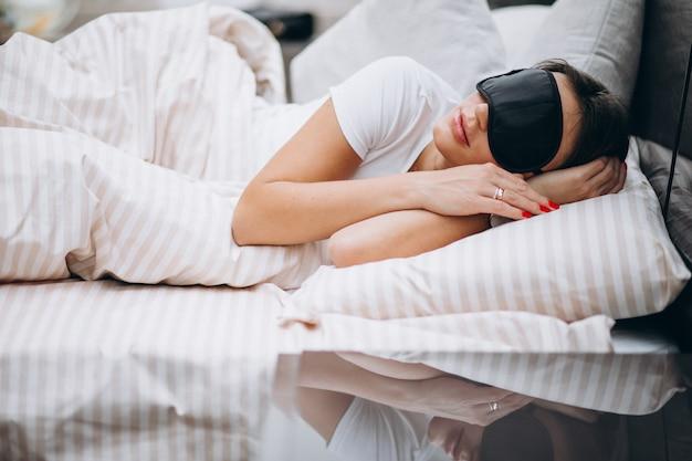 Joven mujer descansando en la cama por la mañana