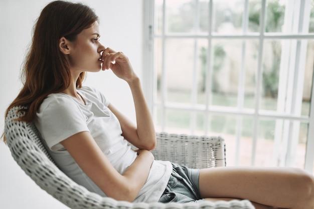 Joven mujer descansando en un sillón en casa junto a la ventana