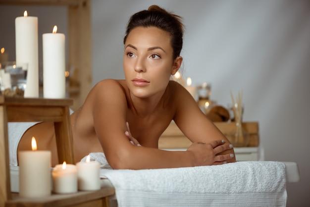 Joven mujer desnuda relajante en el salón de spa.
