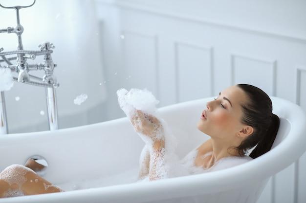 Joven mujer desnuda tomando un relajante baño espumoso