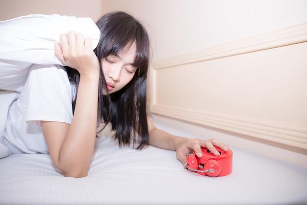 Joven mujer dormida y despertador en el dormitorio en casa