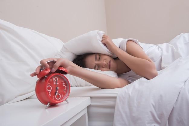 Joven mujer durmiendo en la cama y despertador en el dormitorio en la mañana