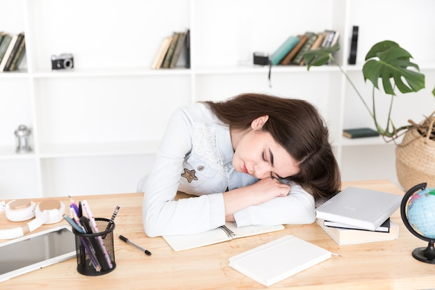 Joven mujer durmiendo en la mesa en el aula