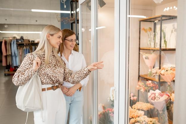 Joven mujer elegante con largo cabello rubio apuntando a uno de los ramos de flores mientras está de pie frente a la pantalla de la tienda con su madre