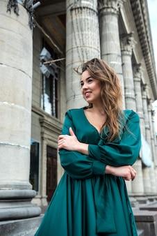Joven mujer elegante relajante y posando para la cámara cerca de columnas en vestido verde en un día de verano perfecto