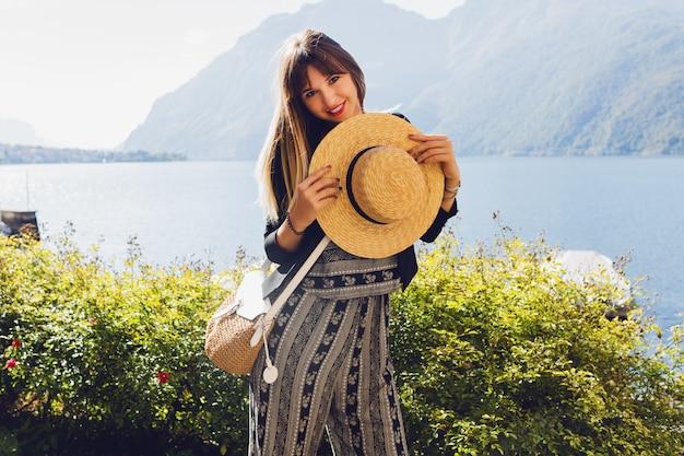 Joven mujer elegante con sombrero de paja en el lago de como