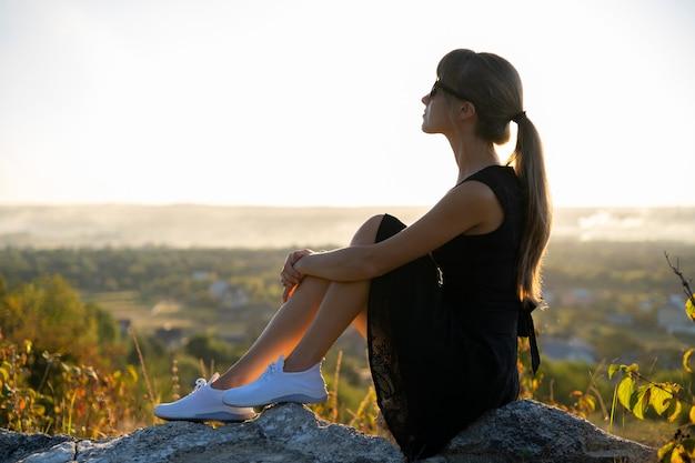 Joven mujer elegante en vestido corto negro y zapatillas blancas sentado en una roca al aire libre relajándose en las noches de verano. dama de moda disfrutando de la cálida puesta de sol en la naturaleza.