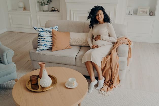 Joven mujer embarazada africana en vestido casual acariciando su vientre mientras está sentado en el sofá en casa