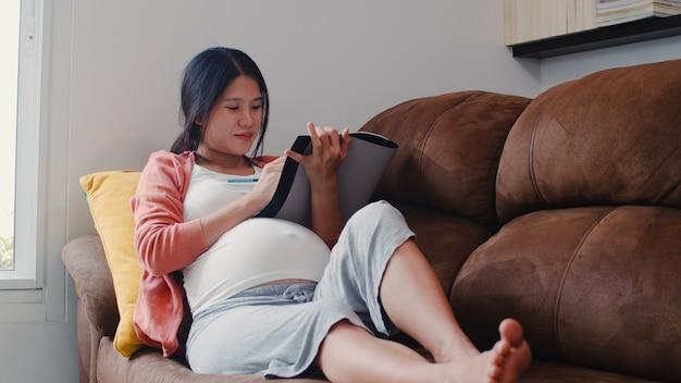 Joven mujer embarazada asiática dibujo bebé en el vientre en el cuaderno. mamá se siente feliz sonriendo positiva y pacífica mientras cuide al niño acostado en el sofá en la sala de estar en casa.