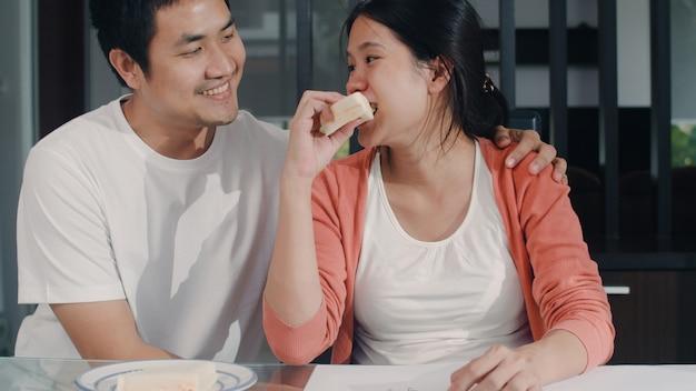 Joven mujer embarazada asiática dibujo bebé en el vientre y la familia en el cuaderno. papá dando sandwich a su esposa mientras feliz sonriendo positivo y pacífico mientras cuide al niño en la mesa en la sala de estar en casa.