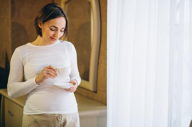 Joven mujer embarazada de pie junto a la ventana y beber café