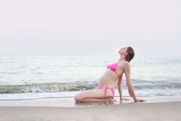 Joven mujer embarazada está practicando yoga sentado en la playa del mar. día de verano