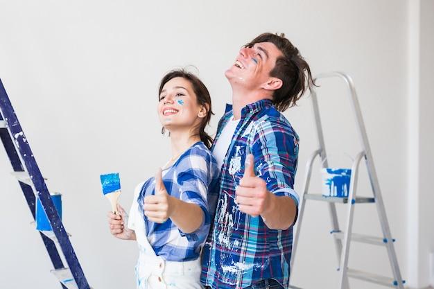 Joven y mujer enamorada y pintando la pared
