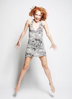 Joven mujer encantadora en vestido saltando