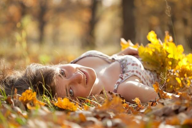 Joven mujer se encuentra en el parque de otoño