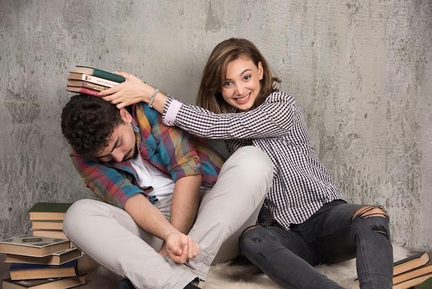 Joven mujer enojada golpeando al hombre con libros