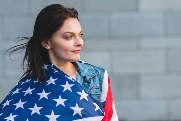 Joven mujer enrollando en la bandera americana