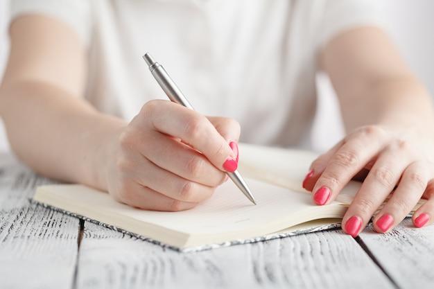 Joven mujer está escribiendo notas y planea su horario
