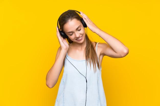 Joven mujer escuchando música sobre pared amarilla aislada cantando