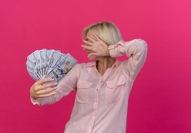 Joven mujer eslava rubia estirando dinero hacia la cámara y escondiendo la cara detrás de la mano aislada sobre fondo rosa con espacio de copia