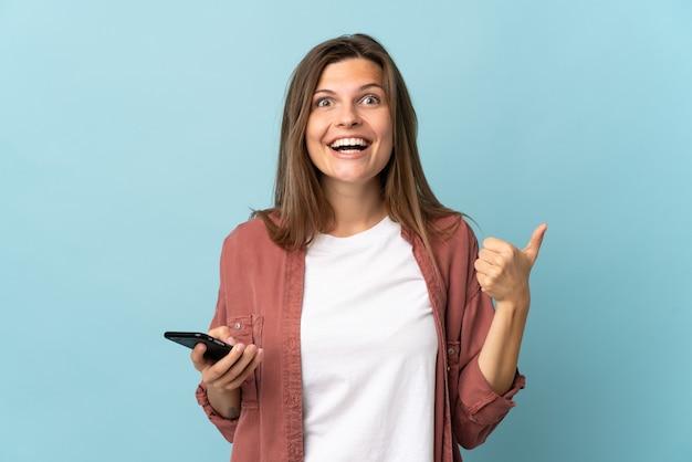 Joven mujer eslovaca aislada sobre fondo azul mediante teléfono móvil mientras hace thumbs up