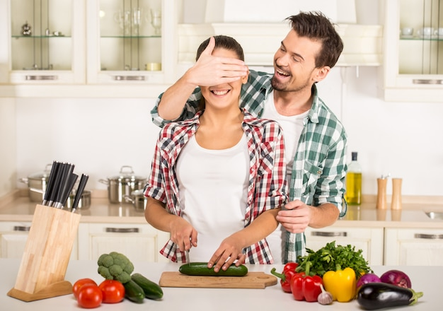Joven mujer y esposo están cocinando con verduras frescas.