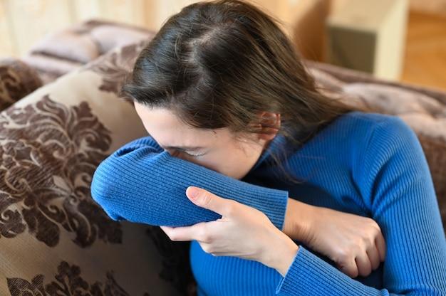 Joven mujer estornuda en el codo