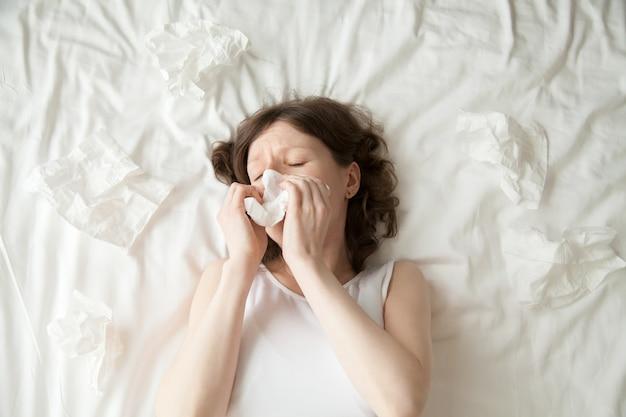 Joven mujer estornudo en el tejido