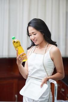 Joven mujer étnica con botella de detergente en casa