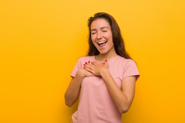 Joven mujer europea aislada sobre fondo amarillo riendo manteniendo sus manos sobre el corazón