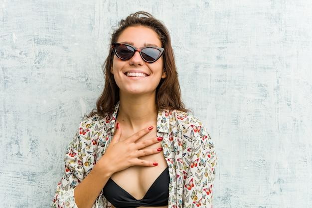 Joven mujer europea con bikini se ríe en voz alta manteniendo la mano en el pecho.