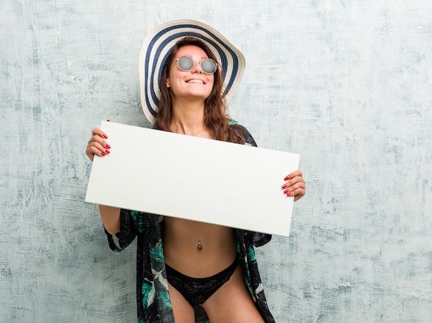 Joven mujer europea con bikini y sosteniendo un cartel