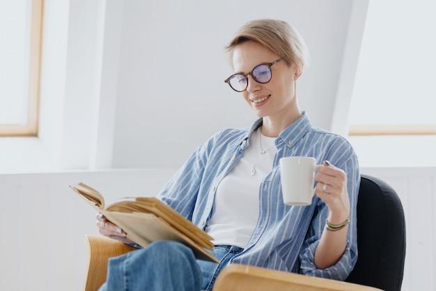 Una joven mujer europea con cabello corto y rubio está bebiendo café o té y leyendo un libro