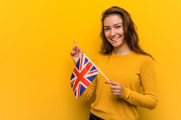 Joven mujer europea sosteniendo una bandera del reino unido sonriendo alegremente señalando con el dedo lejos