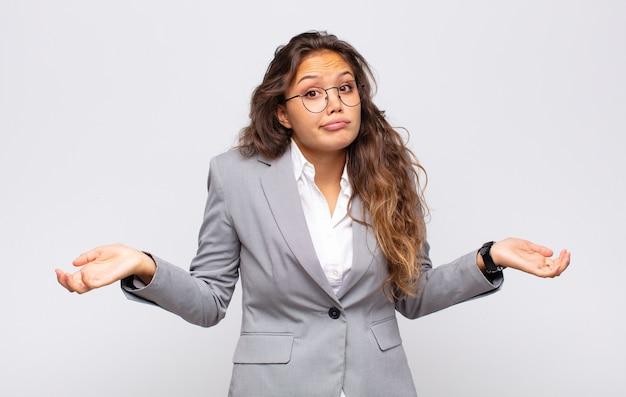 Joven mujer expresiva con gafas y elegante traje posando en la pared blanca