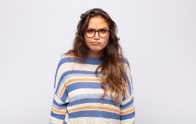 Joven mujer expresiva con gafas posando en la pared blanca
