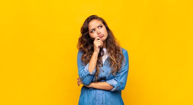Joven mujer expresiva posando en la pared amarilla