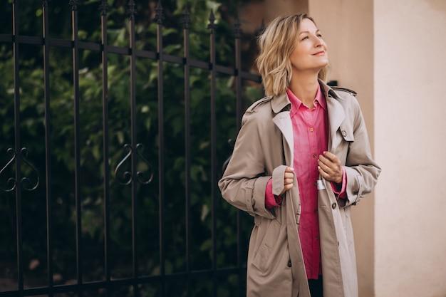 Joven mujer feliz en abrigo de primavera en la ciudad
