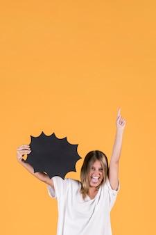 Joven mujer feliz con la boca abierta sosteniendo el bocadillo de diálogo negro y apuntando hacia arriba
